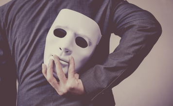 Man-holding-a-mask-behind-his-back